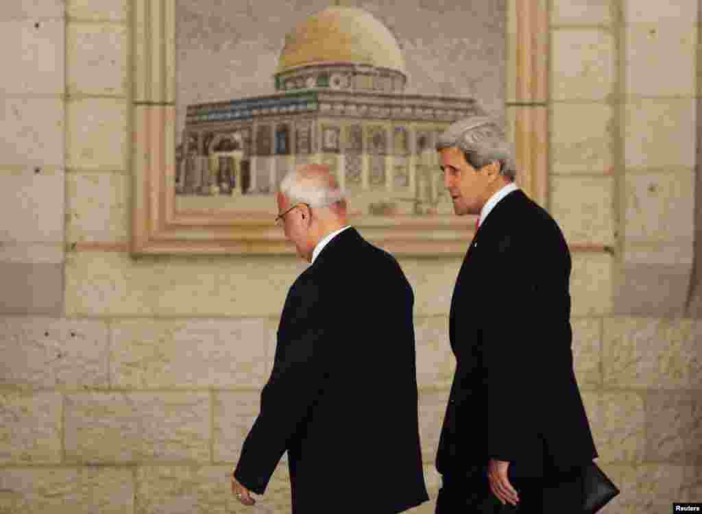 U.S. Secretary of State John Kerry walks with Palestinian Chief Negotiator Saeb Erekat upon his arrival in the West Bank city of Ramallah, May 23, 2013.