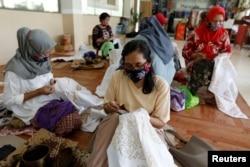 Sejumlah pekerja mengenakan masker sambil membatik di tengah pandemi virus corona (Covid-19) di Jakarta, 1 Juli 2020. (Foto: Willy Kurniawan/Reuters)