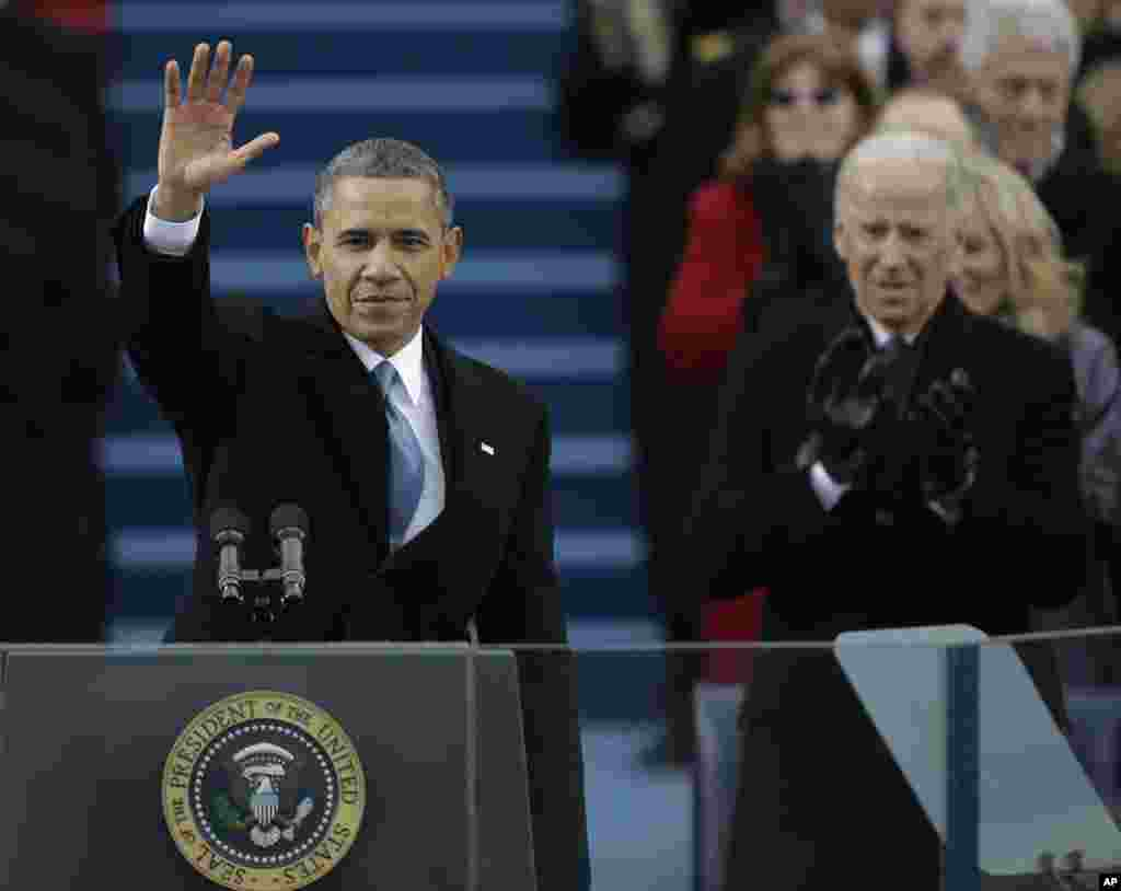 President Barack Obama waves after his speech while Vice President Joe Biden applauds at the ceremonial swearing-in at the U.S. Capitol, Jan. 21, 2013.