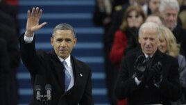 Presiden Barack Obama melambai kepada massa setelah memberikan pidato inaugurasi, sementara Wapres Joe Biden memberikan tepuk tangan (21/1).