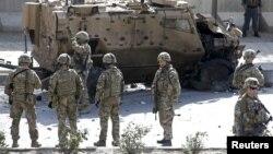 Tentara NATO berdiri di dekat lokasi serangan bunuh diri yang merusak sebuah kendaraan NATO di Kabul, Afghanistan (foto: dok). NATO mengukuhkan serangan bunuh diri terhadap konvoinya di Afghanistan selatan, hari Rabu (2/8).