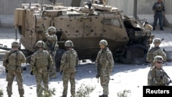 北约军事使命团的士兵站在阿富汗喀布尔发生的自杀式汽车炸弹爆炸现场旁(资料照片)