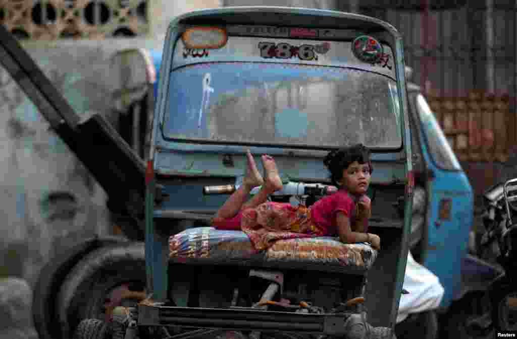 A girl rests on a rickshaw parked along a street in Karachi, Pakistan.