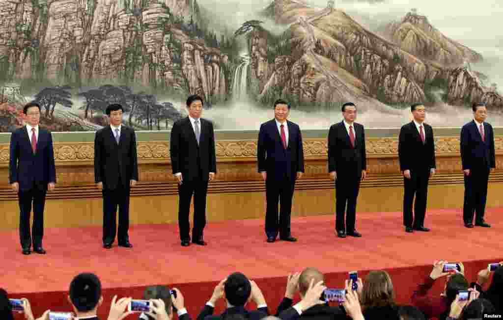 第19届中共中央政治局常委(从左至右)韩正、王沪宁、栗战书、习近平、李克强、汪洋、赵乐际同记者见面(2017年10月25日)。中共十九届一中全会在10月25日结束,新常委亮相。他们的入场顺序是按照地位高低而排列先后的,而并排站立顺序是以中间为大,习近平右侧的李克强是第二号人物,左侧的栗战书是第三号人物。这里说的的左右是对观众来说的,而对习近平来说,李克强在左侧,栗战书在右侧。