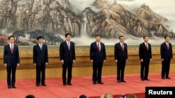 China's new Politburo Standing Committee members (L-R) Han Zheng, Wang Huning, Li Zhanshu, Xi Jinping, Li Keqiang, Wang Yang and Zhao Leji, line up as they meet with the press at the Great Hall of the People in Beijing, China October 25, 2017.