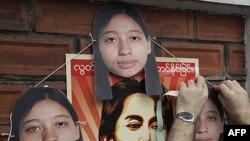 Một nhà hoạt động Miến Điện đang treo ảnh của cô Hla Hla Win, một nhà báo đang bị tù, lên bức tường gần Đại sứ quán Miến Điện trong một cuộc biểu tình ở Bangkok, Thái Lan
