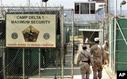 FILE - U.S. military guards walk within Camp Delta military-run prison, at the Guantanamo Bay U.S. Naval Base, Cuba.