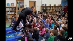 """奥巴马总统在一所小学给学生们朗读""""圣诞节前夜""""的故事后和儿童击掌"""