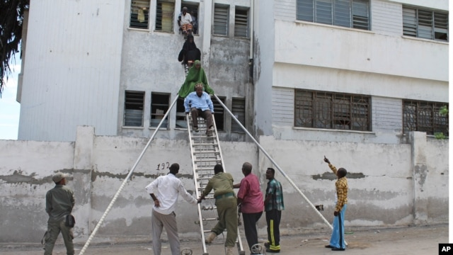Survivors are helped to escape from a window at Mogadishu's court complex in Mogadishu, Somalia, April 14, 2013.
