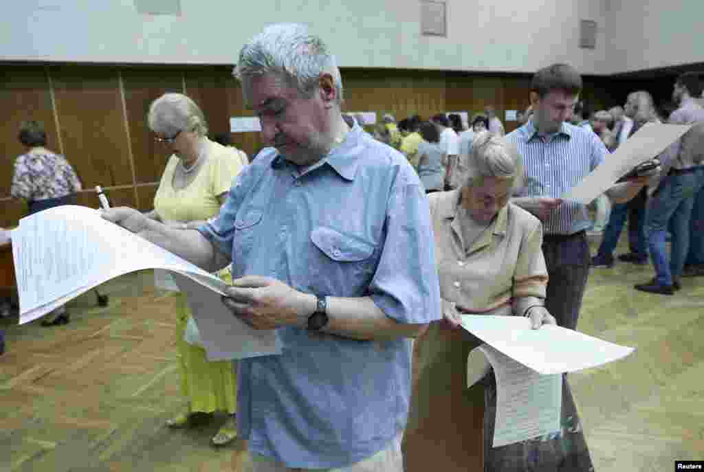 ایک پولنگ اسٹیشن میں ووٹ ڈالنے سے پہلے شہری بیلٹ پیپرز کا مطالعہ کر رہے ہیں۔