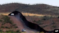 Agentes de la patrulla fronteriza de EE.UU. resguardan la valla que divide la frontera con México cerca de Naco, Arizona.