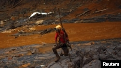 A rescue worker searches for victims at Bento Rodrigues district that was covered with mud after a dam owned by Vale SA and BHP Billiton Ltd. burst, in Mariana, Brazil, Nov. 8, 2015.