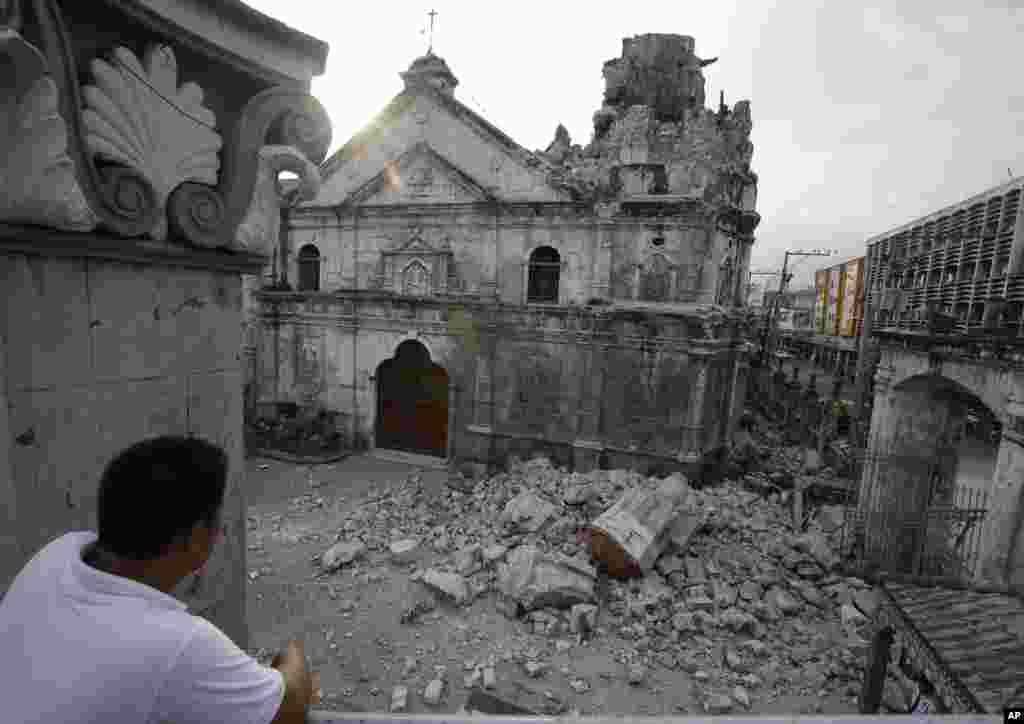 A resident looks at the rubble following an earthquake that hit Cebu city and toppled a church's bell tower, Philippines, Oct. 15, 2013.