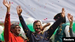 Aam Aadmi (Common Man) Party (AAP) chief and its chief ministerial candidate for Delhi, Arvind Kejriwal (C) waves to his supporters in New Delhi, February 10, 2015.