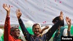 Ketua Partai Aam Aadmi (AAP) dan kandidat Gubernur New Delhi, Arvind Kejriwal (tengah) memberikan salam kepada para pendukungnya seusai memenangkan pemilu (10/2).