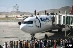 Warga Afghanistan naik ke atas sebuah pesawat saat mereka menunggu di bandara internasional Hamid Karzai di Kabul Senin 16 Agustus 2021, ketika ribuan orang mencoba melarikan diri dari rezim Taliban. (Foto: Wakil Kohsar / AFP)