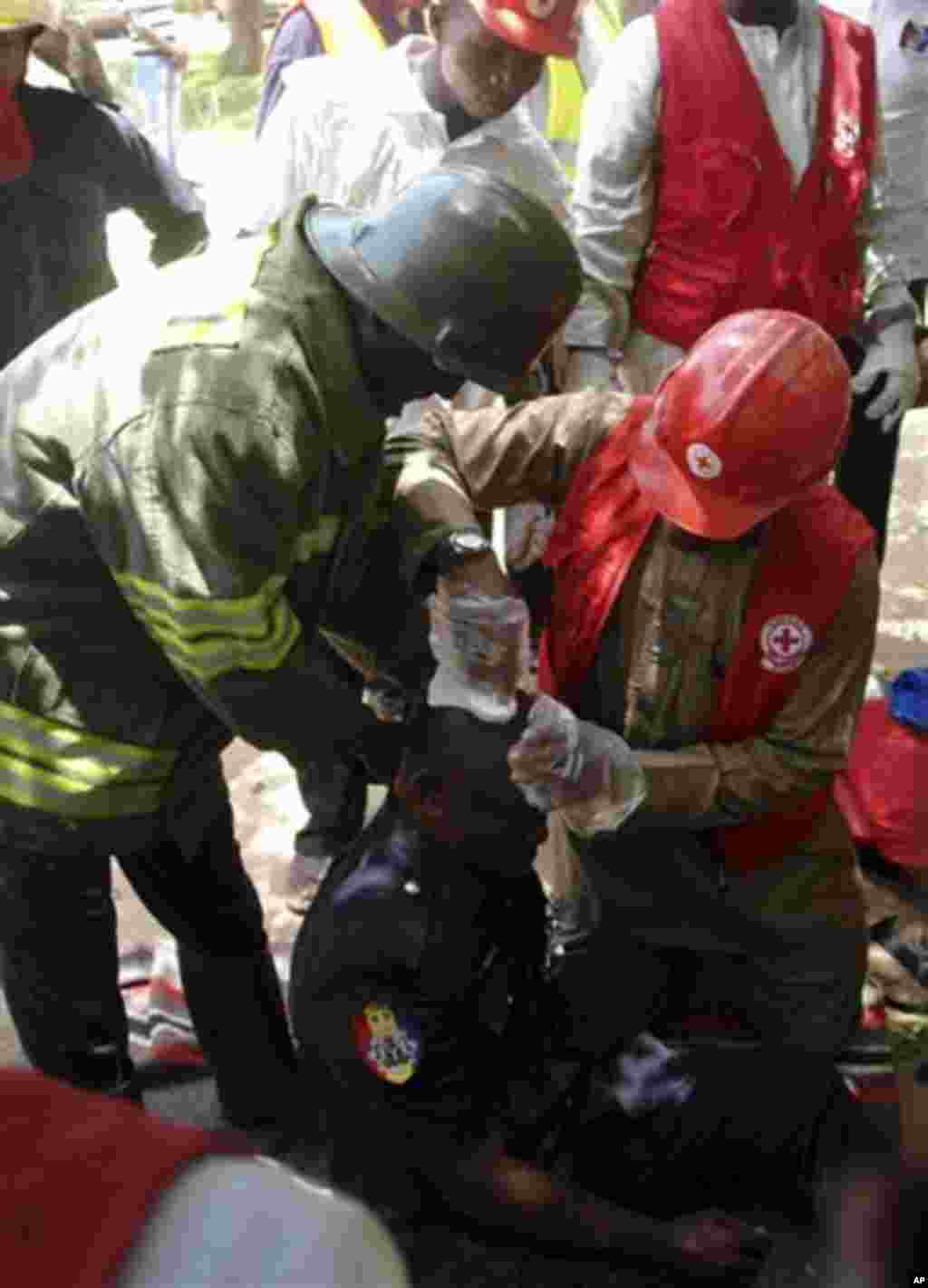 Rescue workers tend to an injured man at the site of the bombed office of ThisDay, an influential daily newspaper in Abuja, Nigeria, Thursday, April. 26, 2012.