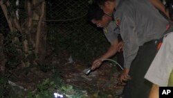 Polisi Burma memeriksa sebuah bom kecil yang meledak di pinggiran ibukota Rangoon (13/10).