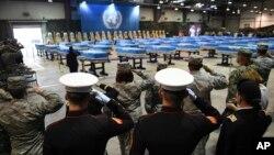 1일 한국 평택시 오산공군기지에서 북한에서 돌려받은 한국전쟁 참전 미군 유해 송환식이 열린 가운데, 군인들이 유해가 담긴 55개의 금속관을 향해 경례하고 있다.