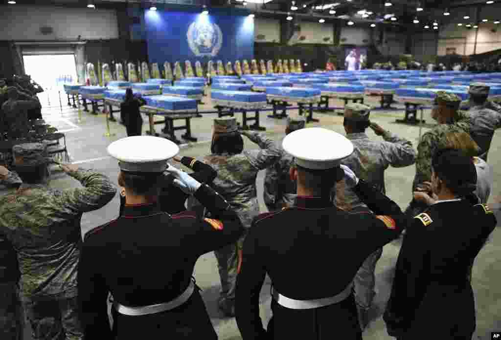 한국 평택시 오산공군기지에서 북한에서 돌려받은 한국전쟁 참전 미군 유해 송환식이 열린 가운데, 군인들이 유해가 담긴 55개의 금속관을 향해 경례하고 있다. 유해는 곧이어 미군 대형 수송기 C-17에 실려 미국 하와이 히캄 공군기지로 옮겨질 예정이다.