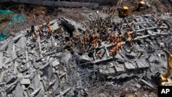 6月29日印度救援人员在南部泰米尔纳德邦一座倒塌的建筑现场搜寻幸存者