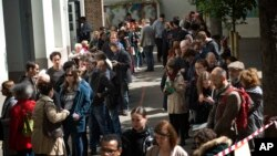 People line up before casting their vote for the first-round presidential election at a polling station in Paris, April 23, 2017.