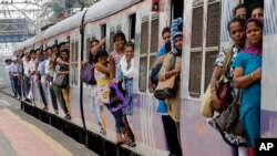 FILE - Commuters hang by doors of a crowded local train in Mumbai, India, July 8, 2014.