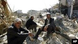 무너진 건물 잔해에 걸터앉은 터키인들