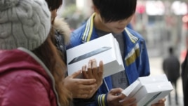 People holding newly-purchased iPad minis wait outside an Apple Store during the China launch for the product, in Shanghai, December 7, 2012.