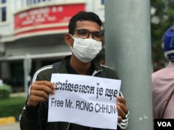 A youth holds a banner calling for the release of Rong Chhun in front of the Olympia Mall of Phnom Penh, August 3, 2020. (Hul Reaksmey/VOA Khmer)