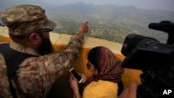 A Pakistan army officer points out the Indian forward area posts to journalists at Bagsar post on the Line of Control that divides Kashmir between Pakistan and India, on October 1, 2016. According to a report, Prime Minister Nawaz Sharif urged spy chief Rizwan Akhtar to take action in the region against three militant groups dedicated to fighting Indian forces.