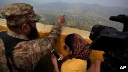 FILE - A Pakistani army officer points out the Indian forward-area posts to journalists at Bagsar post on the Line of Control that divides Kashmir between Pakistan and India, Oct. 1, 2016. The two countries have fought two wars over the disputed Himalayan region.
