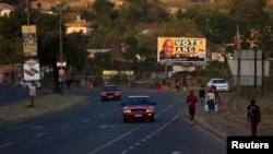 Residents wait for taxi transport beneath election posters in Pietermaritzburg in South Africa's KwaZulu Nataal province, April 29, 2014.
