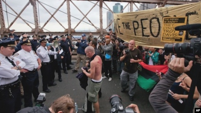 A police officer with a bullhorn addresses a  large group of protesters affiliated with the Occupy Wall Street movement who attempted to cross the Brooklyn Bridge, effectively shutting parts of the roadway down, Saturday, Oct. 1, 2011 in New York.