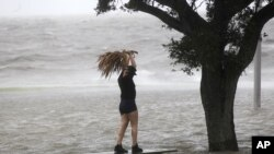 A woman stands on a partially submerged picnic bench in the storm surge from Isaac, on Lakeshore Drive along Lake Pontchartrain, as the storm approaches landfall, in New Orleans, Aug. 28, 2012.