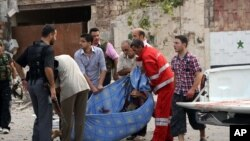 ພວກຜູ້ຊາຍຫາມ ສົບຄົນຕາຍ ໃນເຫດວາງລະເບີດ ສາມບັ້ນ ຕິດຕໍ່ກັນ ໃນເມືອງ Aleppo, ວັນທີ 3 ຕຸລາ 2012.