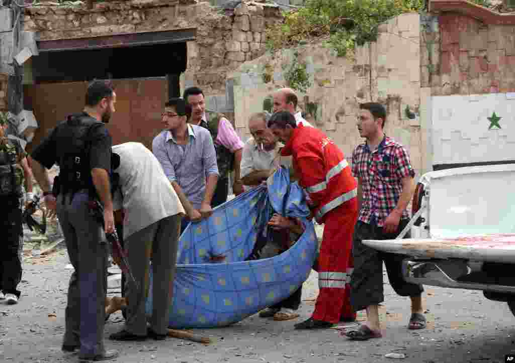 This photo by the Syrian official news agency SANA shows Syrian men carrying a body after bombs bombs exploded in Saadallah al-Jabri square, in Aleppo, Syria, October 3, 2012.