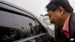 Wasif Ali Khan, a friend of Pakistan's government minister for religious minorities Shahbaz Bhatti looks at the bullet-riddled window of car while he mourns over his death, Islamabad, Pakistan, March 2, 2011.