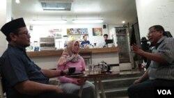 Nur Wulan (tengah) dan Widi Kamidi (kanan) warga Surabaya dalam obrolan warung kopi terkait tragedi di kota mereka. (Foto: VOA/Nurhadi)