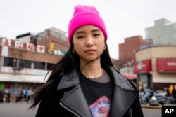 """Teresa Ting stands for a portrait, Wednesday, March 31, 2021, in the Flushing neighborhood of the Queens borough of New York. """"It literally could have been my mother had it been the wrong place, wrong time,"""" Ting said of that attack. (AP Photo/John Minchilo)"""