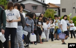 Residents queue up for drinking water at an elementary school in Takatsuki, Osaka, June 18, 2018, after a strong quake hit the area during the morning rush hour.