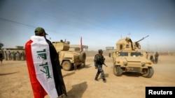 伊拉克軍隊收復摩蘇爾附近的一個城鎮後,披上伊拉克旗慶祝。