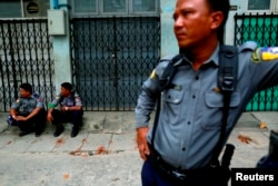 Police officers guard a Muslim residential area in Mandalay, Myanmar, July 3, 2014.