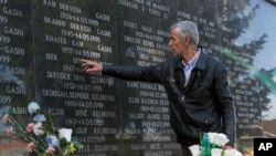 FILE - A survivor of the Cuska massacre points out the names of family members as he visits a cemetery in the village of Cuska, Kosovo, on Feb. 11, 2014.