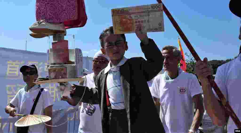 小男孩扮演財政司司長陳茂波在烈日下派錢。(美國之音湯惠芸拍攝)