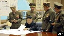 Pemimpin Korea Utara, Kim Jong-un tengah mendiskusikan rencana penyerangan dengan para pejabat tinggi angkatan bersenjata Korut dalam rapat darurat, 29 Maret 2013. (AFP Photo/KCNA VIA KNS).