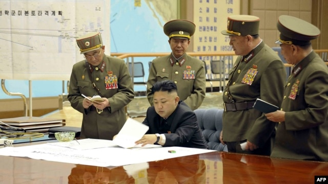 North Korea's official Korean Central News Agency on March 29, 2013 shows, according to KCNA, North Korean leader Kim Jong Un discussing the strike plan with North Korean officers during an urgent operation meeting at the Supreme Command in an undisclosed location. (Courtesy - AFP Photo/KCNA VIA KNS)