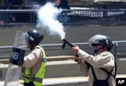 A Bolivarian National Police officer fires tear gas toward demonstrators during a protest in Caracas, Venezuela, April 8, 2017.