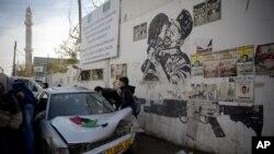 Palestiniens examinant le véhicule utilisé dans une tentative d'attaque contre des soldats israéliens, faubourg de Ramallah, Cisjordanie, le 16 décembre 2015. (AP Photo/Majdi Mohammed)