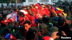 El ataúd del expresidente Hugo Chávez cubierto de ropa lanzada por la gente en las calles de Caracas. sus restos podrían ir al Panteón Nacional.